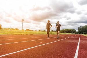 Dos corredores trotando en la pista de carreras, el deporte y el concepto de actividad social foto