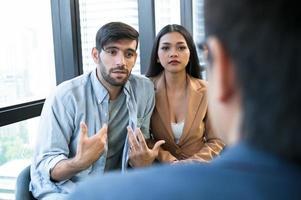 Psychotherapist inquiring about symptoms occurring within mind from patients with mental health problems in hospital. Group psychotherapy for support and helping worried man to change negative mindset photo