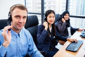 Group of young profession call center operator agent with headsets working in office. Business telemarketing service people concentrating on having conversation work and talking to customer friendly photo