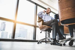 Portrait of happy handsome business man with headset in modern office with city urban building background. Businessman sitting on chair. Caucasian man relaxing in customer care service call center photo