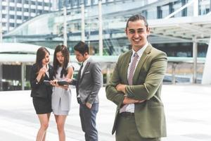 Smiling young businessman looking into camera with his arms crossed and teammates background in urban. Modern business office team at outdoors in city. Business people and Leadership lifestyle concept photo
