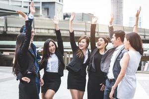 retrato de exitoso grupo de gente de negocios al aire libre urbano. felices empresarios y empresarias levantando la mano como equipo en gesto de satisfacción. exitoso grupo de personas sonriendo después del logro foto
