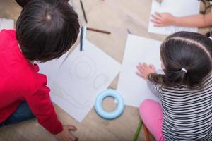 Group of preschool student and teacher drawing on paper in art class. Back to school and Education concept. People and lifestyles theme.  Room in nursery photo