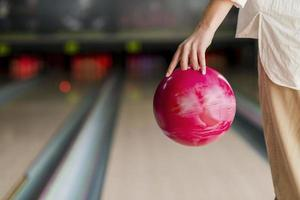 Person holding red bowling ball photo