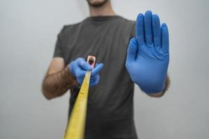 Man with gloves holding tape measurer, social distancing photo