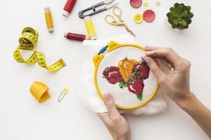 Manos cosiendo lindo diseño de frutas sobre fondo blanco. foto