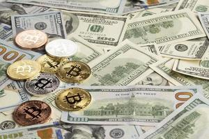 Different colored bitcoin coins on dollar bills photo