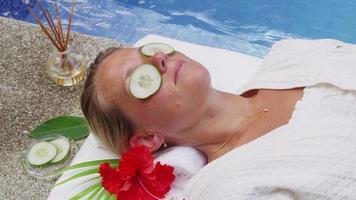 la donna che posa a bordo piscina presso la spa ottiene i cetrioli sugli occhi. girato in rosso epico per una risoluzione 4k, uhd, ultra hd di alta qualità. video