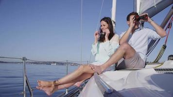 pareja joven en velero juntos mirando con binoculares. filmado en rojo épico para una resolución de alta calidad de 4k, uhd, ultra hd. video