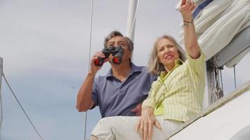 seniorpar som tittar genom kikare på segelbåt tillsammans. sköt på röd epik för högkvalitativ 4k, uhd, ultrahd -upplösning. video