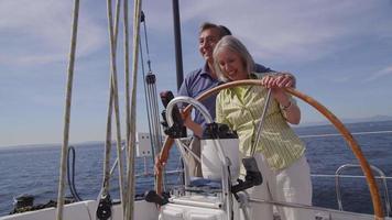 senior paar achter het stuur van zeilboot samen. geschoten op rood episch voor hoge kwaliteit 4k, uhd, ultra hd-resolutie. video
