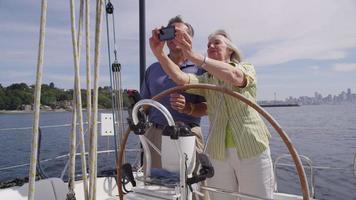 seniorpar bakom ratten på segelbåt tillsammans. sköt på röd epik för högkvalitativ 4k, uhd, ultrahd -upplösning. video