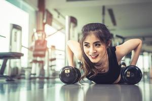 Mujer joven asiática haciendo flexiones con mancuernas en el piso en el gimnasio y el equipo de fondo. concepto de ejercicio de entrenamiento y deporte. concepto de salud y felicidad. tema de belleza y cuerpo foto