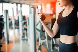 mano de mujer deportiva levantando pesas para entrenamiento con pesas a mano para bombear el músculo bíceps con fondo de gimnasio. entrenamiento y concepto de acumulación corporal. gimnasio de ejercicio interior y tema de club deportivo. foto