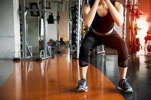 Mujer fitness haciendo ejercicios en cuclillas para quemar grasa y fortalecer las piernas en el gimnasio deportivo con equipamiento deportivo en segundo plano. la belleza y el cuerpo construyen el concepto. club deportivo y tema aeróbico. foto