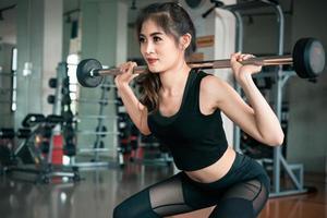 mujer deportiva levantando peso en el gimnasio. ejercicio de entrenamiento y concepto de construcción corporal. tema de levantamiento de pesas y belleza foto