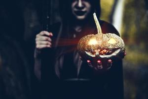 Pumpkin in witch hand. Old woman holding pumpkin in dark forest. Halloween day and Mystery concept. Fantasy of magic theme photo