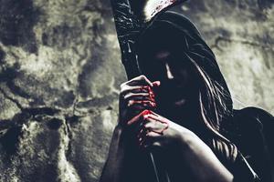 bruja demonio con reaper de pie delante del fondo de la pared del grunge. halloween y concepto religioso. ángel demonio y tema de satanás foto
