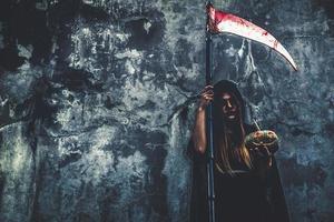 bruja demonio con reaper sobre fondo de pared grunge. halloween y concepto religioso. ángel demonio y tema de satanás foto