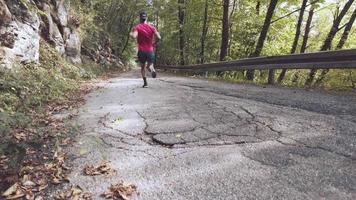 un athlète en descente sur une route goudronnée en montée video