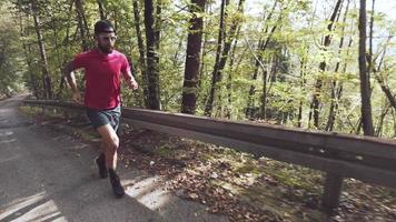een atleet die op een bergopwaartse asfaltweg rent video