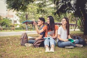 Grupo de estudiantes universitarios asiáticos leyendo libros y clases especiales de tutoría para el examen en el campo de hierba al aire libre. concepto de aprendizaje de la felicidad y la educación. volver al concepto de escuela. tema de adolescentes y personas foto