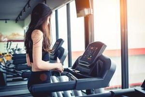 Asian woman using smart phone when workout or strength training at fitness gym on treadmill. Relax and Technology concept. Sports Exercise and Health care theme. Happy and Comfortable mood photo