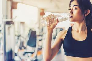 Asian woman drinking pure drinking water for freshness after workout or exercise training in fitness gym with fitness equipment background. Relax and Rest concept. Strength and Fitness training theme photo