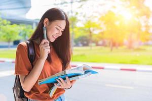Mujer asiática joven universitaria haciendo la tarea y leyendo libros para el examen final en el campus. concepto de universidad y estudiante. concepto de estilo de vida y belleza. adolescente y tema de aprendizaje foto