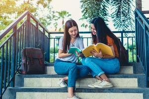 Two Asian beauty girls reading and tutoring books for final examination together. Student smiling and sitting on stair. Education and Back to school concept. Lifestyles and People portrait theme photo
