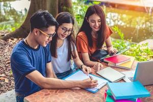 Grupo de estudiantes universitarios asiáticos leyendo libros y clases especiales de tutoría para el examen en la mesa al aire libre. concepto de aprendizaje de la felicidad y la educación. volver al concepto de escuela. tema de adolescentes y personas foto