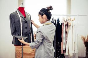 Asian female fashion designer girl making fit on the formal suit uniform clothes on mannequin model. Fashion designer stylish showroom. Sewing and tailor concept. Creative dressmaker stylist photo