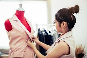 Asian female fashion designer girl making fit on the formal dress uniform clothes on mannequin model. Fashion designer stylish showroom. Sewing and tailor concept. Creative dressmaker stylist photo