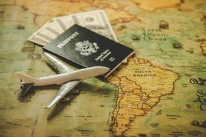 Top view of tourist planning props and travel accessories with American passport, airplane and US dollar banknote money on old grunge style map. Holiday and vacation. Tourism long weekend concept photo