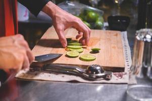Primer plano de la mano del camarero profesional cortando limón para hacer jugo de limonada con un cuchillo en el club nocturno. chef haciendo bebidas para los huéspedes en el restaurante pub. concepto de comida y bebida foto