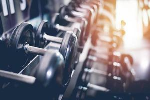 Black steel dumbbell set. Close up of dumbbells on rack in sport fitness center. Workout training and fitness gym concept. Healthy and well being concept. Sport equipment and tool theme photo