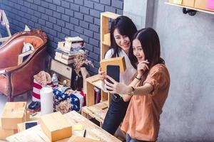 dos mujeres se tomaron una selfie con un teléfono móvil mientras vendían juntas en línea. concepto de estilos de vida de negocios y personas. chicas tailandesas toman una foto mientras compran en línea