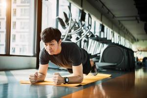 Portrait of Asian fitness man doing planking exercise in gym. People lifestyle and Sport workouts concept photo