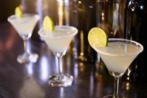 Primer plano de bebidas de limonada en copas de martini en el bar en el club nocturno. cerrar el alcohol en el restaurante pub. concepto de comida y bebida foto