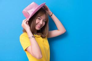 Beauty woman posing with pink hat in front of blue wall background. Summer and vintage concept. Happiness lifestyle and people portrait theme. Cute gesture and pastel tone photo
