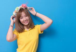 Beauty woman posing with flower hat in front of blue wall background. Summer and vintage concept. Happiness lifestyle and people portrait theme. Cute gesture and pastel tone photo