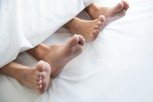 Close up of couple barefoot under blanket in bedroom in honeymoon vacation holiday in long weekend at home. Relaxation of sexual and romantic people after wedding ceremony. Valentines day love theme photo