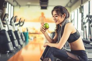 Asian woman holding and looking green apple to eat with sports equipment and treadmill in background. Clean food and Healthy concept. Fitness workout and running theme photo
