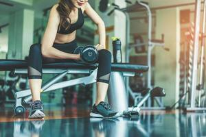 Asian young woman playing dumbbell workout exercise in fitness gym. Relax and Health care concept. Sports and weight training theme photo