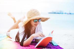 Beauty Asian woman have vacation on beach. Girl wearing wing hat and reading book on colorful mat near sea. Lifestyle and happy life concept. Travel and holiday theme photo