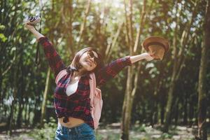 Happiness Asian traveler woman in forest with spread arms and enjoy fresh air. Relax time and Adventure concept. Vacation and Holiday concept. Woods and countryside background theme photo