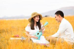 Two Asian young couples in autumn meadow field doing picnic in honeymoon trip in white clothes, ukulele guitar and fruits basket. People lifestyle and wedding concept. Nature and travel day concept photo