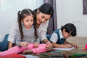 Mother teaching children in drawing class. Daughter and son painting with colorful crayon color in home. Teacher training students in art classroom. Education and Learning development of kids theme photo
