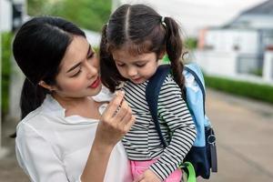mamá alimenta a su hija con bocadillos antes de ir a la escuela. volver al concepto de escuela y educación. hogar, dulce hogar y familia feliz tema foto