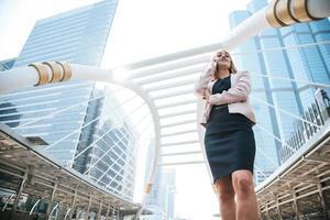 empresaria de belleza mediante teléfono móvil para comunicarse con los clientes de la ciudad. concepto de negocio y tecnología. tema de la metrópoli foto